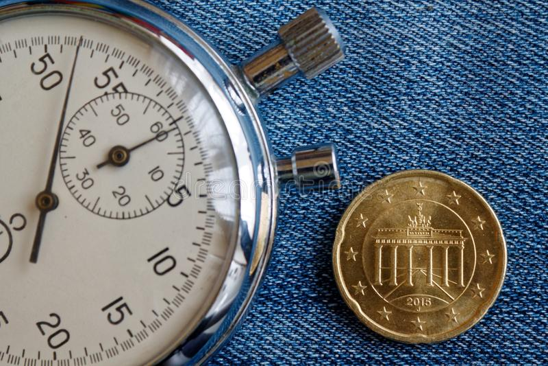 与二十在破旧的蓝色牛仔布背景-企业背景的欧分(后部)和秒表的衡量单位的欧洲硬币 免版税图库摄影