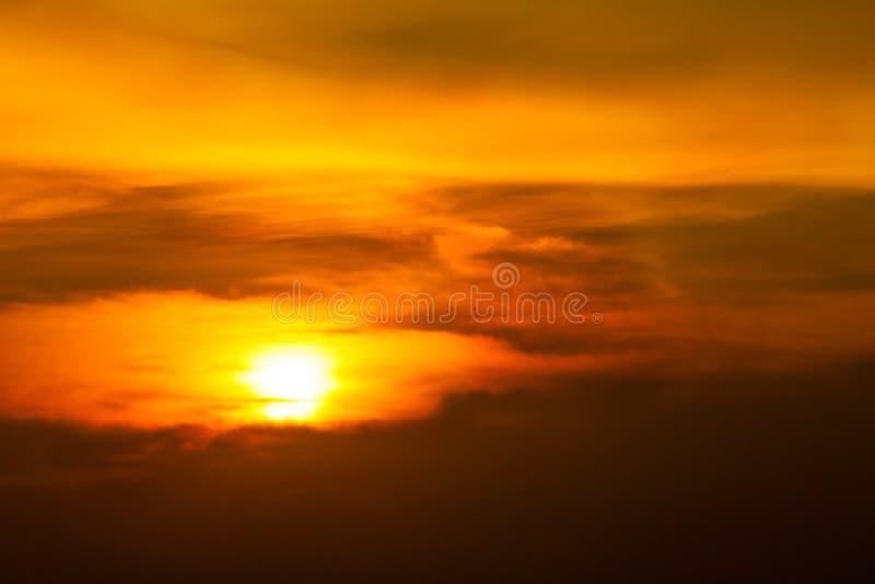 与云彩、光线和其他大气作用的日出日落 在云彩的精采橙色日出与明亮的黄色太阳 免版税库存照片