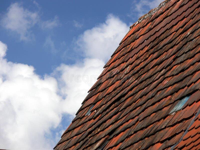 与云彩和深红砖屋顶的天空蔚蓝 图库摄影