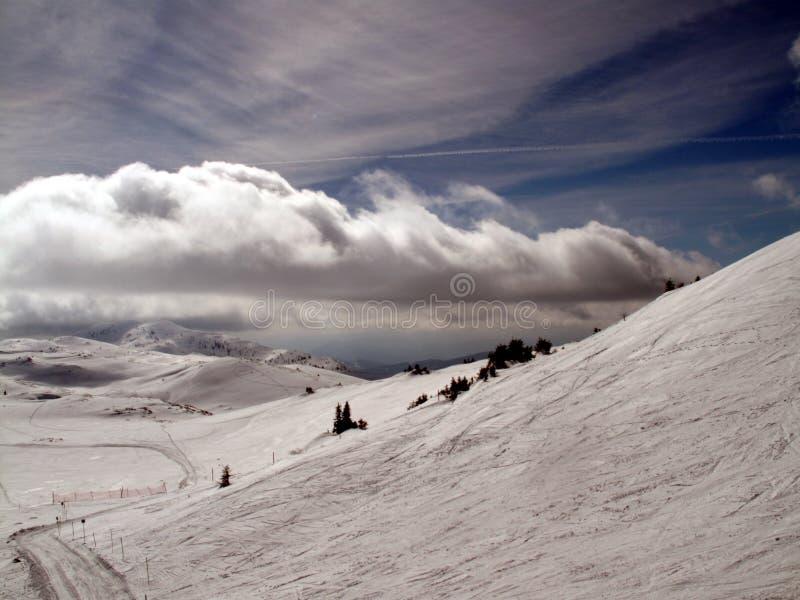 与云彩和雪的山 免版税库存照片