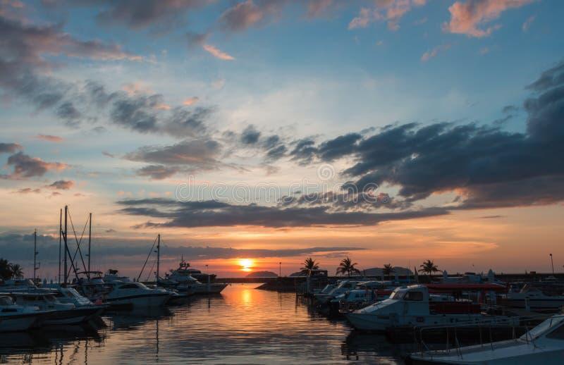 与云彩天空的日落在有游艇的码头 库存照片