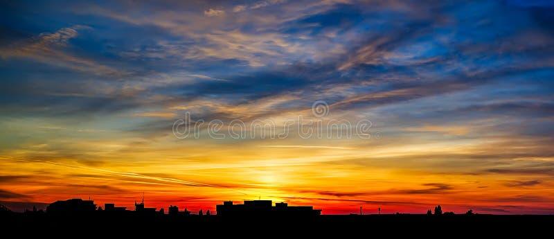 与云彩的五颜六色的日落在城市 库存图片