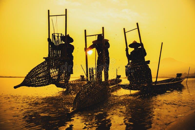 与云彩的日出在有渔船的海洋 库存照片