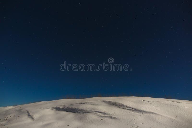 与云彩的星在一个多雪的山土坎的夜空 外层空间背景被拍摄在满月下 库存图片