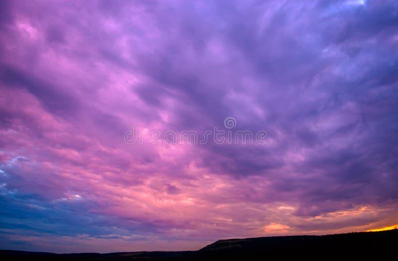 与云彩的紫罗兰色日落 免版税库存图片