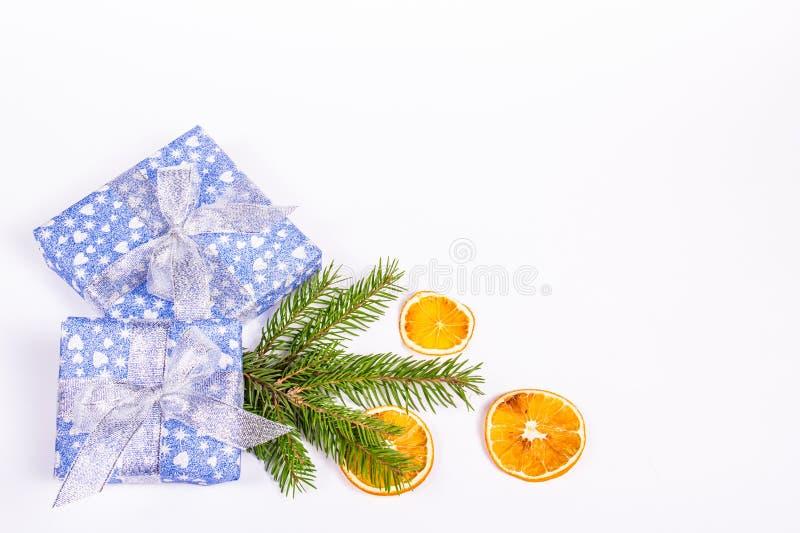 与云杉的分支、礼物和桔子的圣诞节背景 在白色背景的精采礼物盒 免版税图库摄影