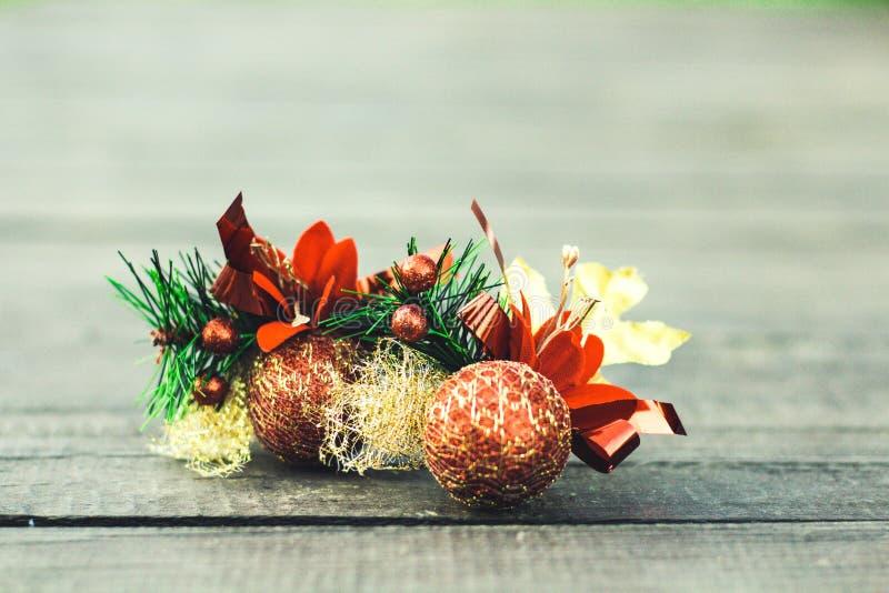 与云杉绿色小树枝的两个橙色圣诞节球在木背景的 免版税库存图片