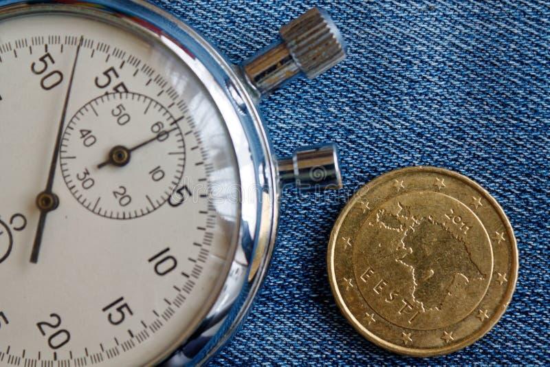 与五十在破旧的蓝色牛仔布背景-企业背景的欧分(后部)和秒表的衡量单位的欧洲硬币 免版税库存照片