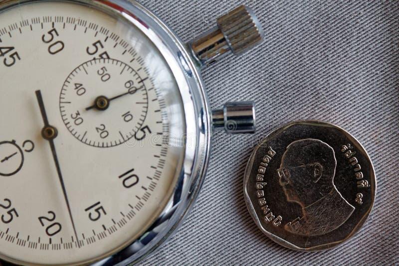 与五在灰色牛仔布背景-企业背景的泰铢(后部)和秒表的衡量单位的泰国硬币 免版税库存图片