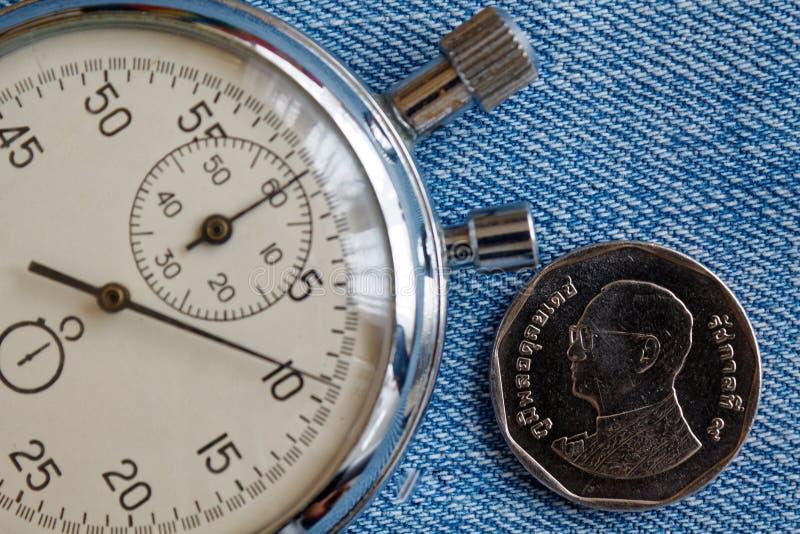 与五在蓝色牛仔裤背景-企业背景的泰铢(后部)和秒表的衡量单位的泰国硬币 库存照片