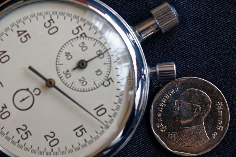 与五在黑牛仔布背景-企业背景的泰铢(后部)和秒表的衡量单位的泰国硬币 库存图片
