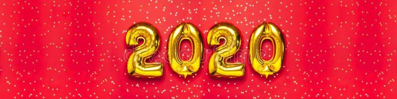 与五彩纸屑的2020个可膨胀的金黄数字以在红色背景的星的形式 新年冬天装饰,假日标志 图库摄影