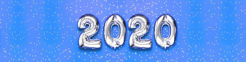 与五彩纸屑的2020个可膨胀的银色数字以在蓝色背景的星的形式 新年冬天装饰,假日标志 库存图片