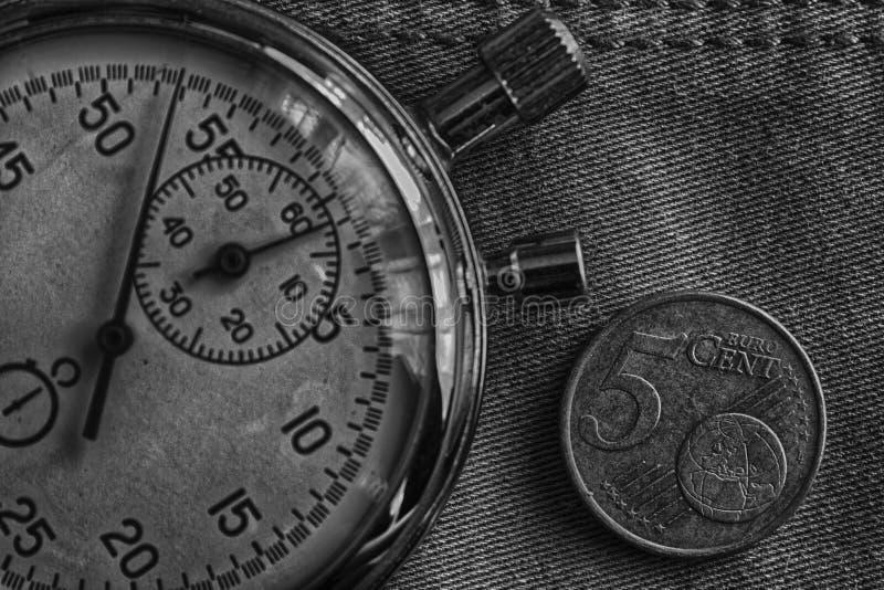 与五欧分和秒表的衡量单位的欧洲硬币在破旧的牛仔布背景-企业背景 免版税库存图片