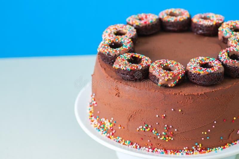 与五颜六色的五彩纸屑和被烘烤的c的富有的巧克力生日蛋糕 库存图片