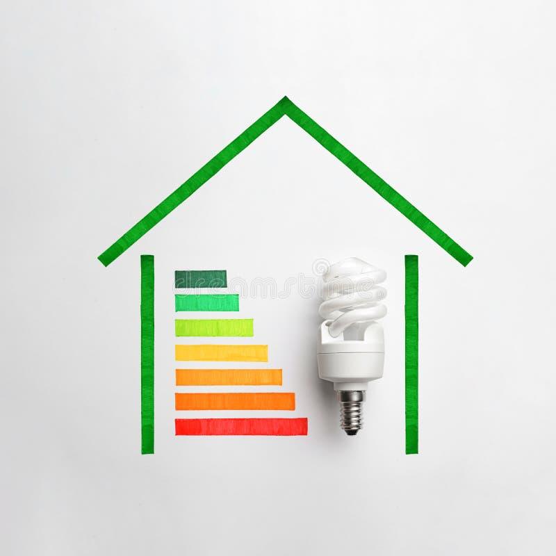 与五颜六色的图的平的被放置的构成和在白色的电灯泡 节能概念 免版税库存照片