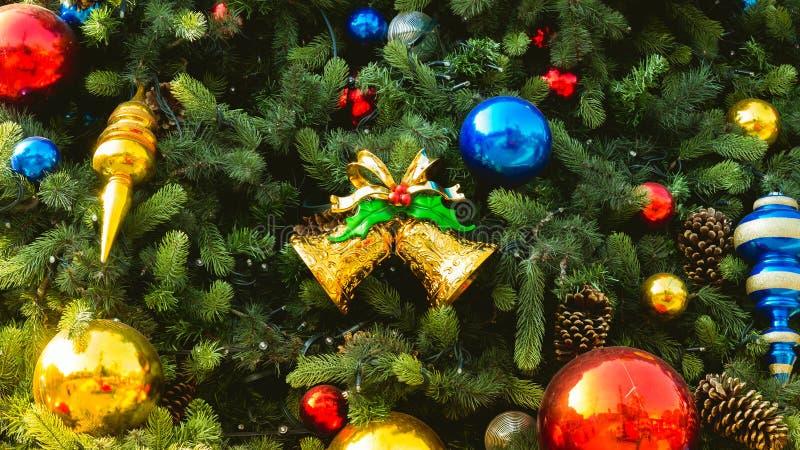 与五颜六色的圣诞节球的装饰的圣诞树和金响铃装饰 图库摄影