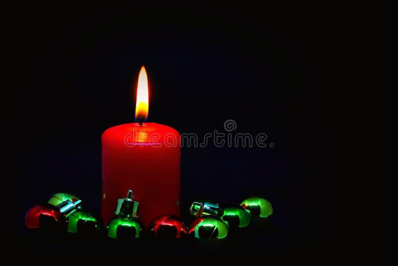 与五颜六色的小圣诞节球的红色蜡烛 库存图片