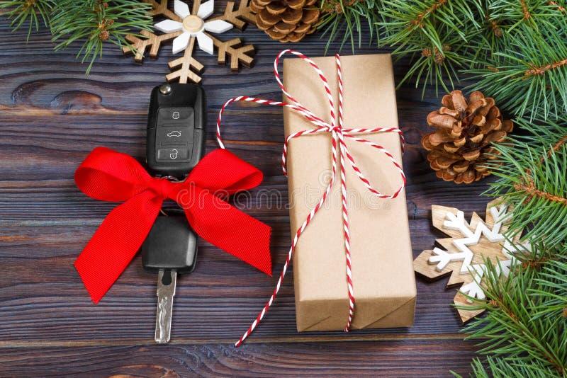 与五颜六色的弓的汽车钥匙与在木背景的礼物盒和圣诞节装饰 免版税库存图片