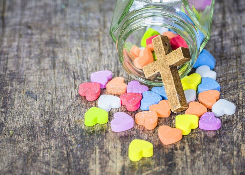 与五颜六色的心脏象的木十字架在木桌上 免版税库存图片