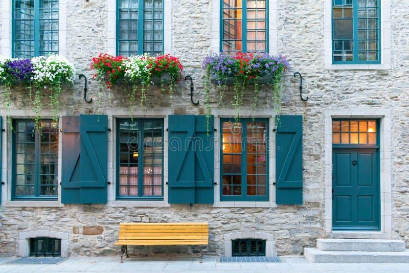 与五颜六色的快门和窗槛花箱的石大厦在魁北克 库存照片