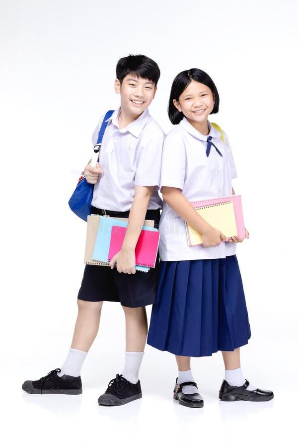 与五颜六色的文具的两个亚洲人微笑的学校孩子 库存照片