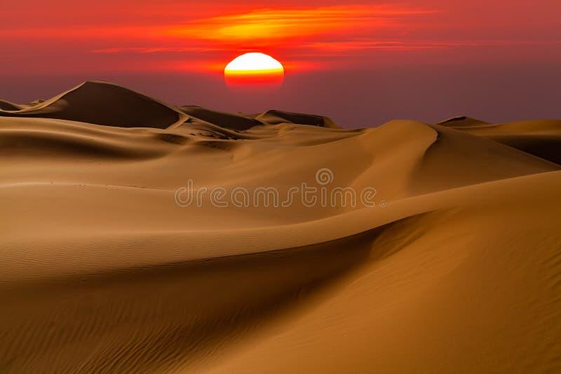 与五颜六色的日落的美好的沙漠风景 日落太阳 库存图片