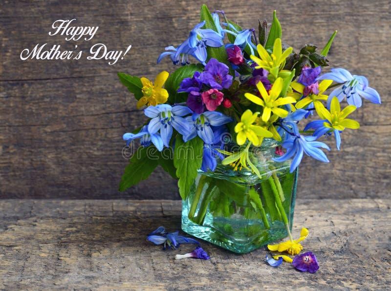 与五颜六色的春天的愉快的母亲` s天贺卡在老木背景的一个玻璃花瓶开花 库存图片
