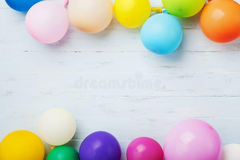 与五颜六色的气球的党或生日横幅在蓝色木背景顶视图 平的位置样式 库存图片