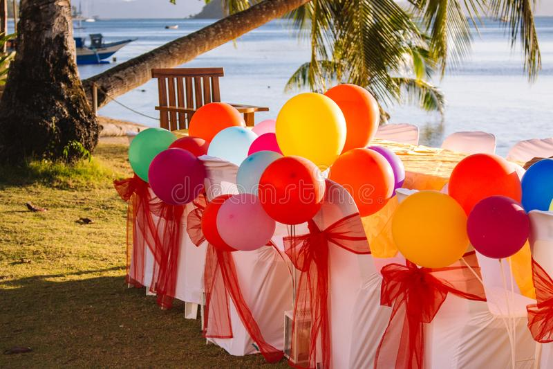 与五颜六色的气球的欢乐桌在与棕榈树和小船的海滩背景 生日快乐庆祝概念 免版税图库摄影