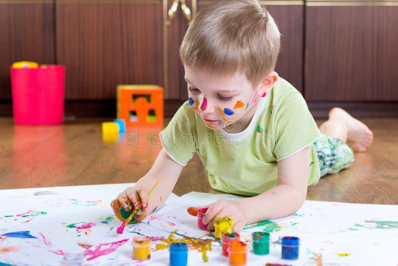 与五颜六色的油漆的小男孩绘画 库存照片