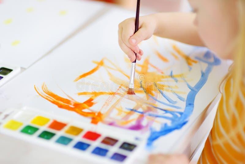 与五颜六色的油漆的逗人喜爱的小女孩图画在托儿 创造性的孩子绘画在学校 库存图片
