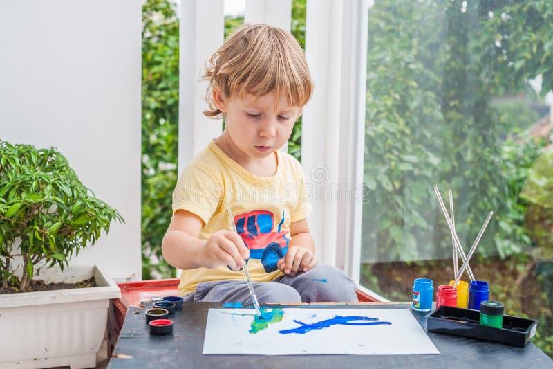 与五颜六色的油漆的逗人喜爱的小男孩绘画 库存照片
