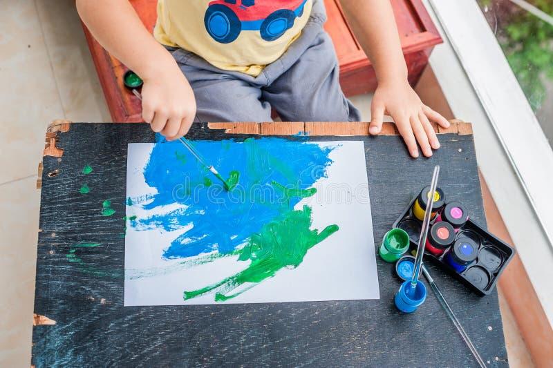 与五颜六色的油漆的逗人喜爱的小男孩绘画 免版税库存照片