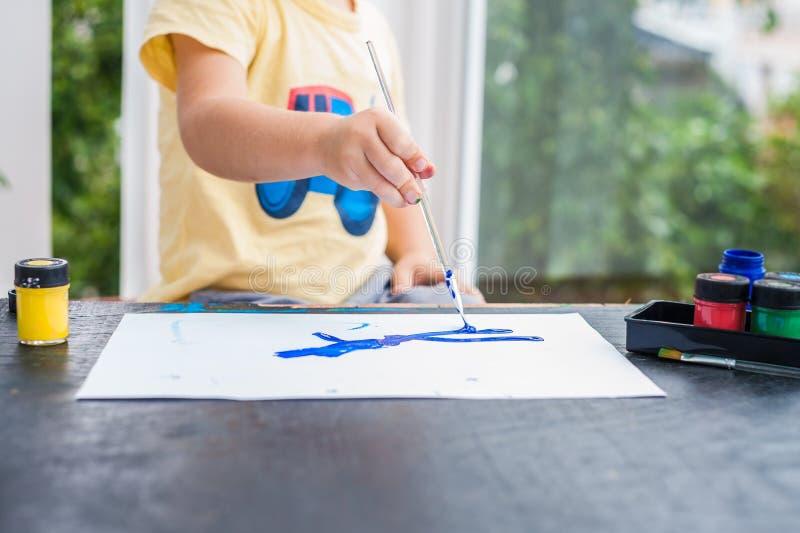 与五颜六色的油漆的逗人喜爱的小男孩绘画 图库摄影