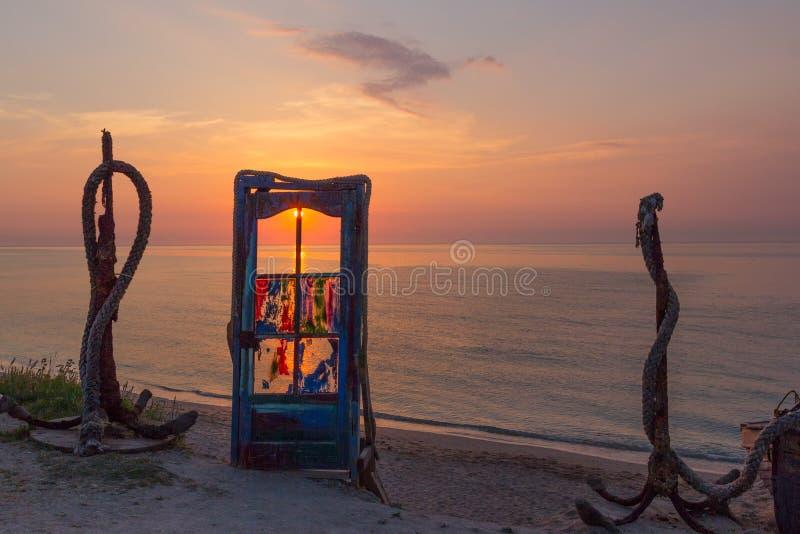 与五颜六色的玻璃和船锚的一个蓝色门在日出的海滩 免版税库存照片