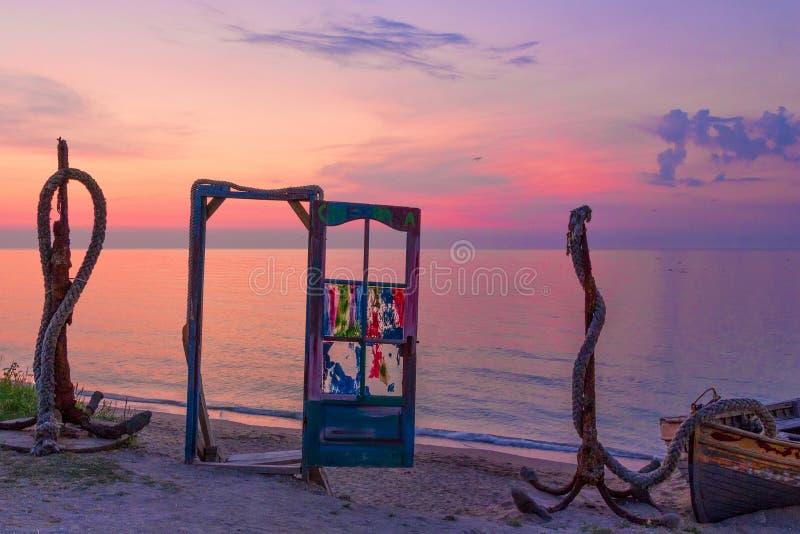 与五颜六色的玻璃和船锚的一个蓝色门在日出的海滩 库存图片