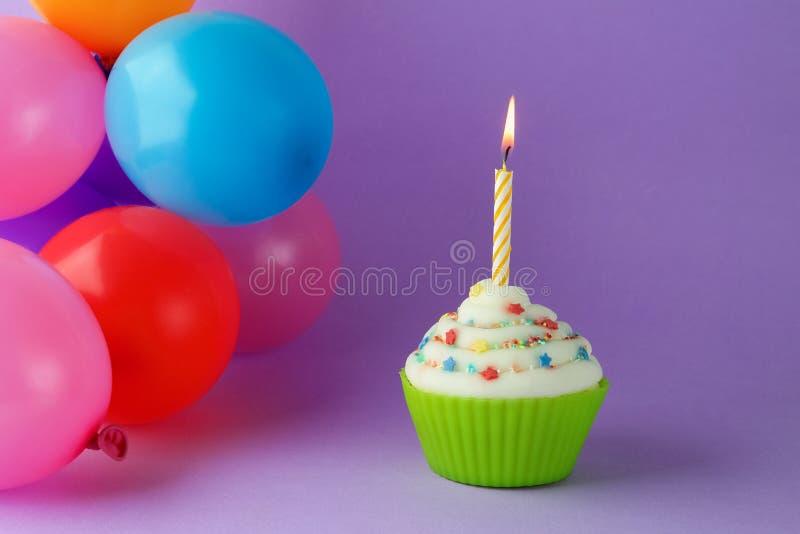 与五颜六色的生日蜡烛和气球的杯形蛋糕 免版税图库摄影