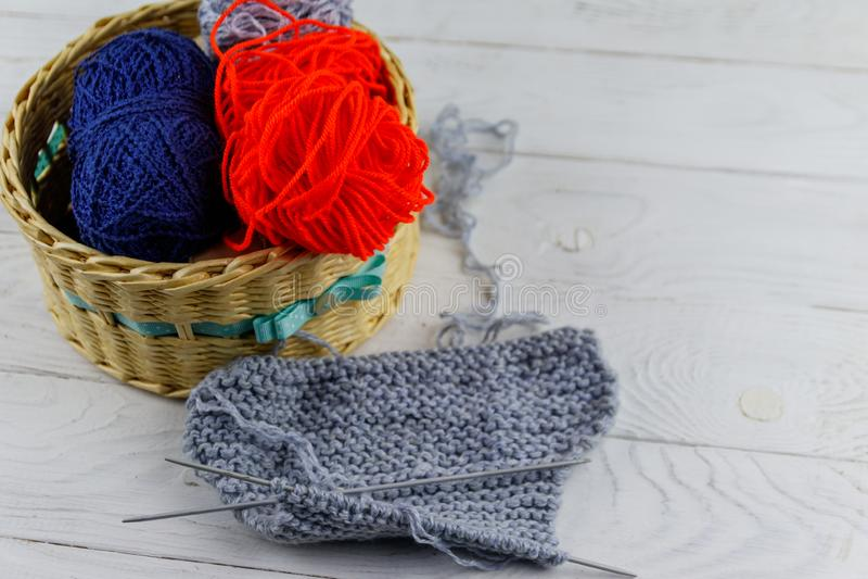 与五颜六色的编物纱,编织针和编织的柳条筐在白色木桌上 库存图片