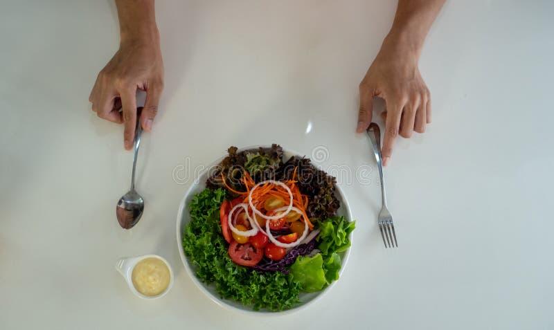 与五颜六色的菜的沙拉盘用奶油沙司和器物在人前面的一张白色桌上服务 图库摄影
