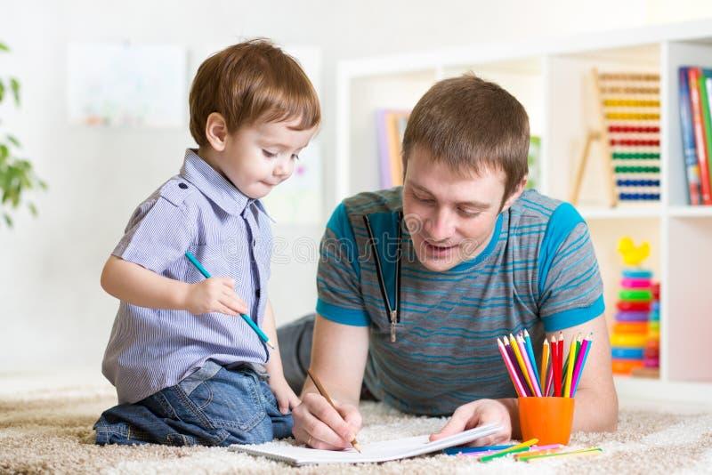 与五颜六色的铅笔的儿童和父亲图画 库存照片