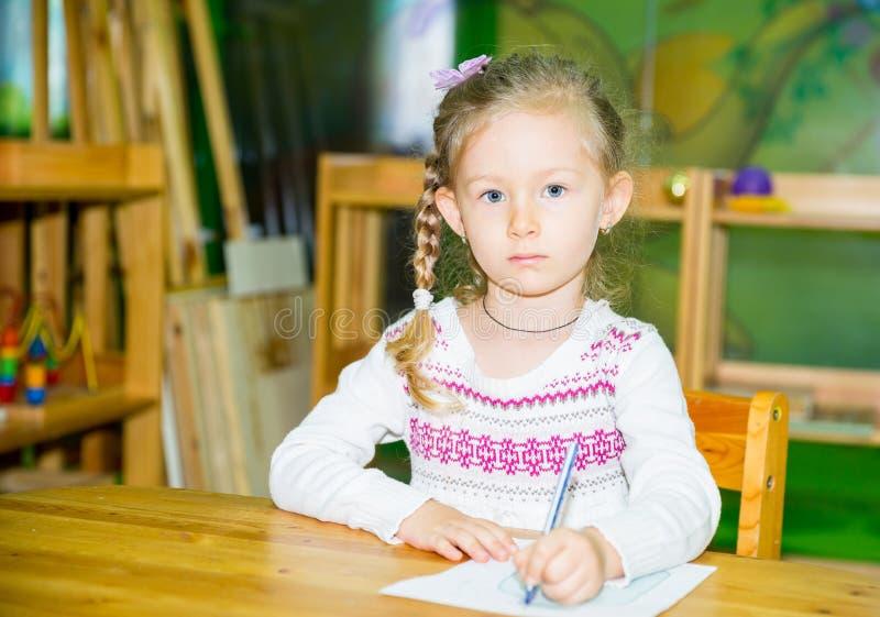 与五颜六色的铅笔的可爱的儿童女孩图画在托儿所屋子里 孩子在幼儿园在蒙台梭利幼儿园类 库存照片