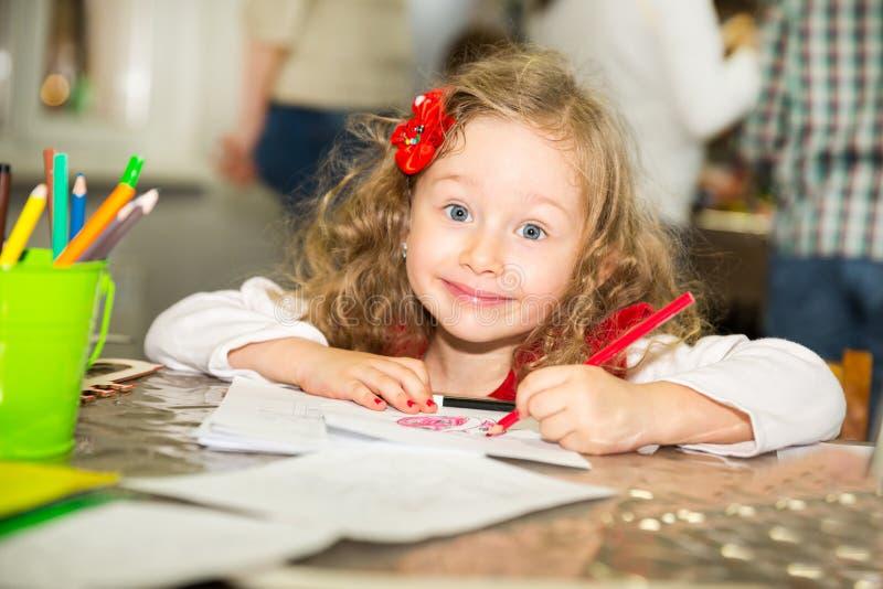 与五颜六色的铅笔的可爱的儿童女孩图画在托儿所屋子里 孩子在幼儿园在蒙台梭利幼儿园类 库存图片