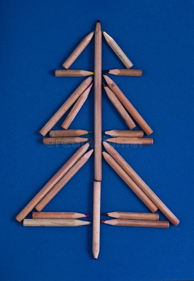 与五颜六色的铅笔的圣诞卡片当圣诞树-蓝色纸板背景 免版税库存图片