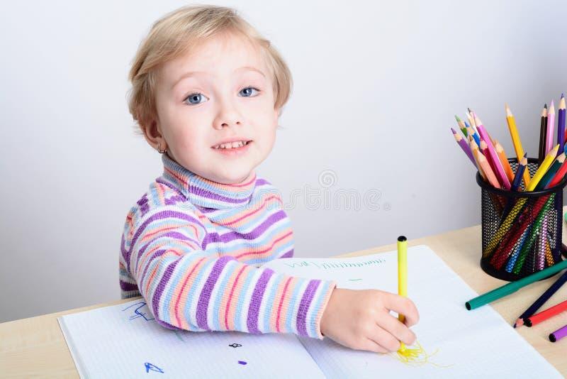与五颜六色的铅笔的女孩图画 免版税库存照片