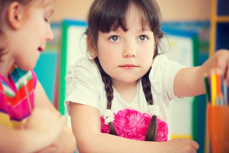 与五颜六色的铅笔的逗人喜爱的女孩图画在幼儿园 库存图片