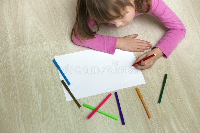 与五颜六色的铅笔蜡笔的逗人喜爱的儿童女孩图画在白皮书 艺术教育,创造性概念 免版税库存照片