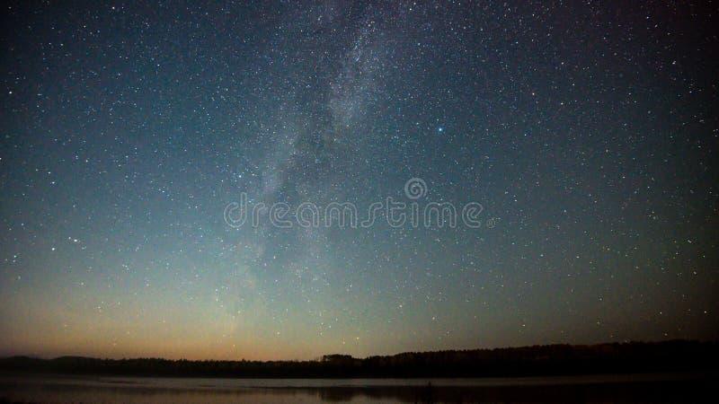 与五颜六色的银河的夜风景和在山的黄灯 与小山的满天星斗的天空在夏天 美丽 免版税库存照片