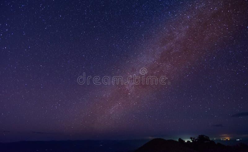 与五颜六色的银河的夜风景和在山的黄灯 免版税图库摄影