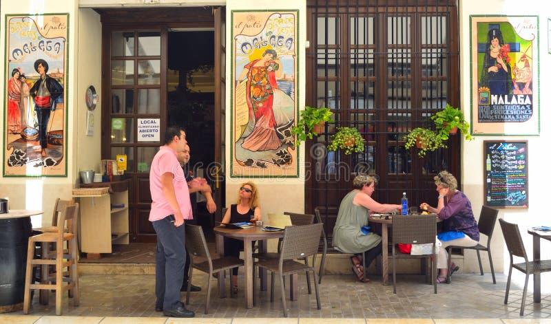 与五颜六色的陶瓷砖的西班牙塔帕纤维布酒吧在墙壁,享受午餐的顾客上 免版税库存图片